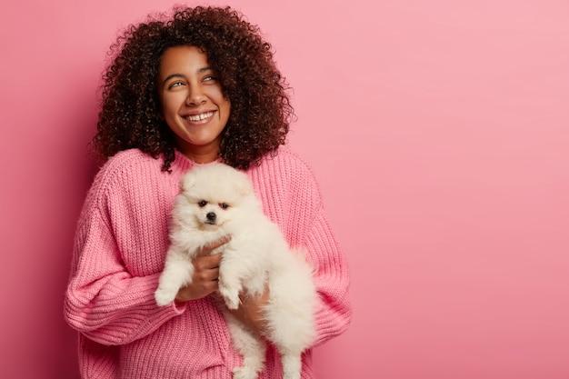 Chica afroamericana positiva sostiene spitz de pomerania, está de buen humor, presiona a la mascota cerca del cuerpo