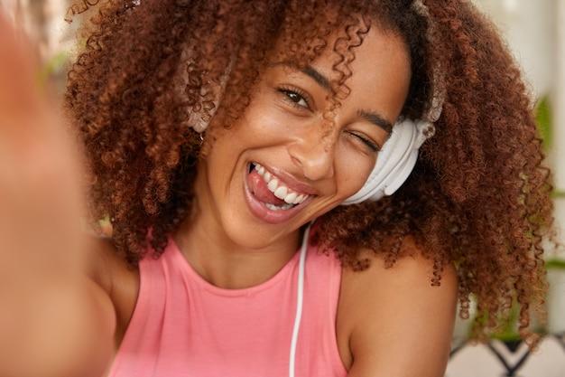 La chica afroamericana rizada positiva parpadea, muestra la lengua, está de buen humor, escucha la melodía en los auriculares, estira la mano y hace un retrato selfie con un dispositivo irreconocible