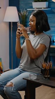 Chica afroamericana tomando foto de dibujo con smartphone