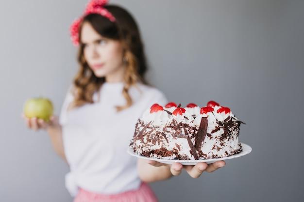 Chica agraciada pensativa sosteniendo pastel de chocolate y pensando en la dieta. desenfoque de retrato de mujer morena con pastel cremoso en primer plano.