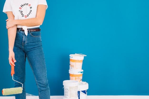 Chica al lado de cubos de pintura