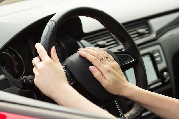 La chica al volante presiona una bocina, el concepto de conducción segura
