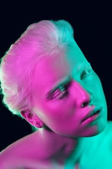 Chica albina con piel blanca, labios naturales y cabello blanco en luz de neón aislada sobre fondo negro de estudio.