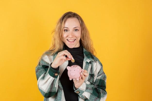Chica con una alcancía y una moneda en sus manos