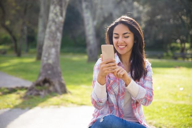 Chica alegre alegre feliz de usar conexión inalámbrica en parte