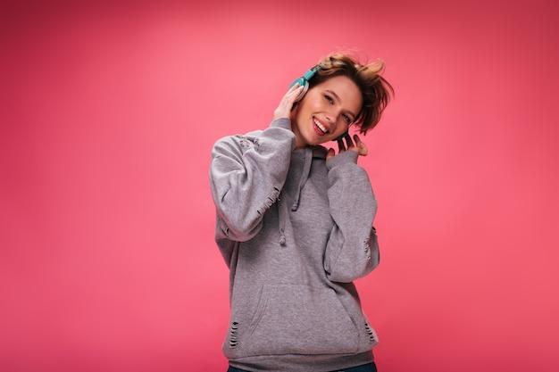 Chica alegre en auriculares brillantes posando sobre fondo aislado. bastante joven en sudadera con capucha gris escuchando música sobre fondo rosa