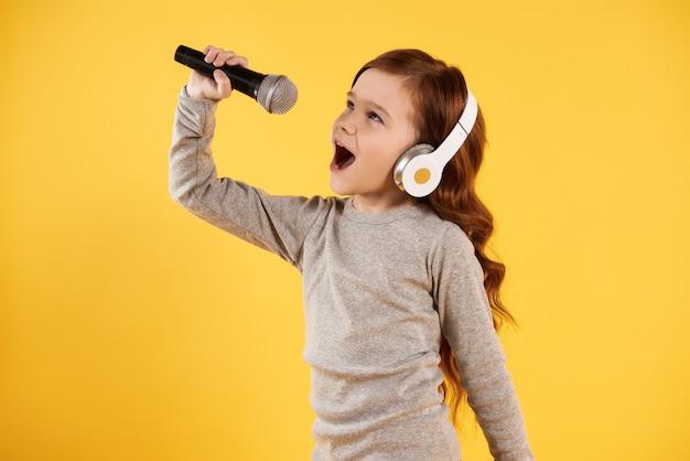 Chica alegre en auriculares está cantando karaoke.