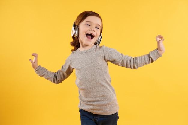 Chica alegre con auriculares escuchando música.