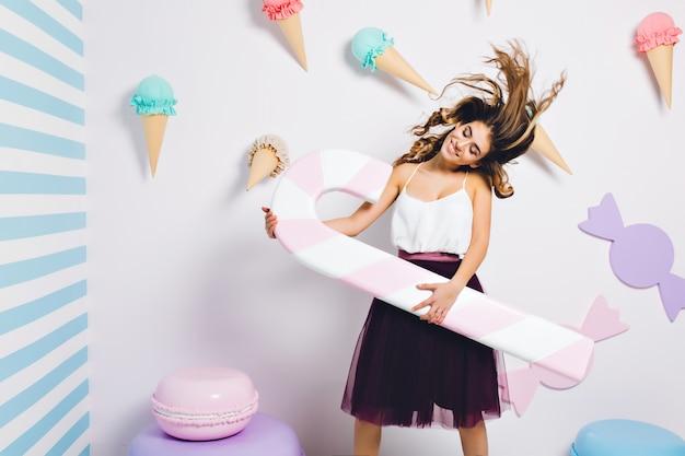 Chica alegre bailando con el pelo rizado ondeando y los ojos cerrados sosteniendo un bastón de caramelo rosa. mujer joven atractiva en vestido encantador divirtiéndose en la fiesta temática y posando en la pared decorada con dulces