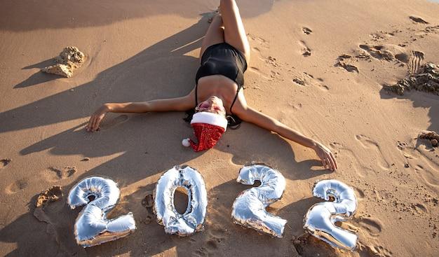 Chica alegre con bolas de plata en forma de números 2022 cerca del concepto de mar de año nuevo