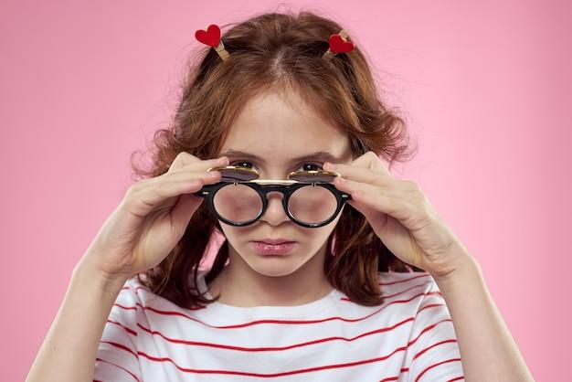 Chica alegre con coletas gafas de sol camiseta rayada estilo de vida fondo rosa. foto de alta calidad