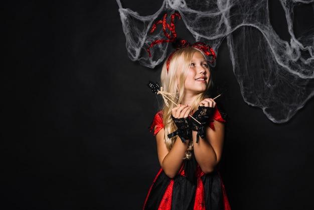 Chica alegre en traje rojo con juguetes de halloween