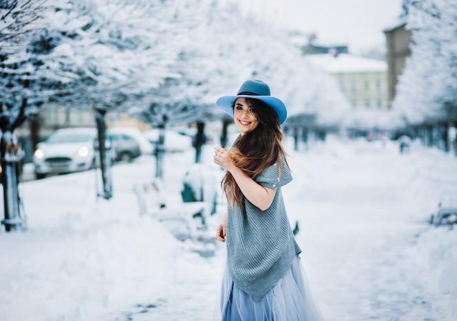 Chica alegre en vestido de verano ligero, suéter y sombrero camina por el callejón del parque