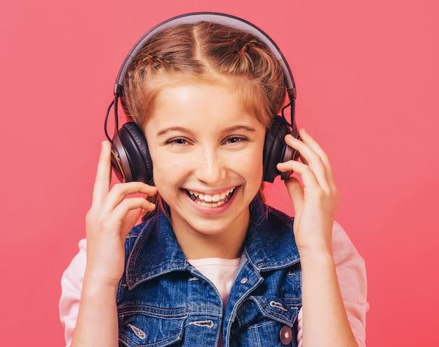 Chica alegre escucha música en auriculares