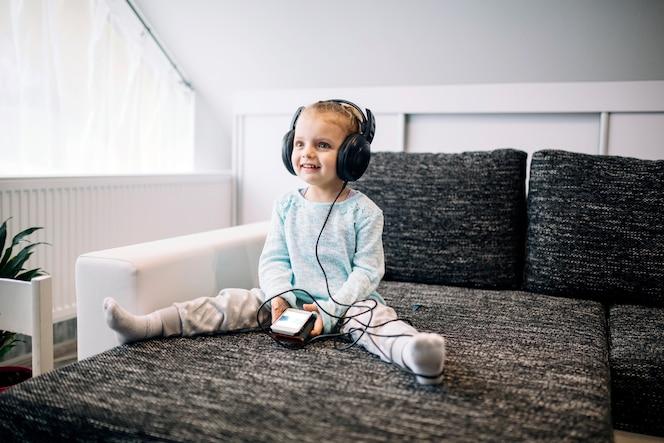 Chica alegre escuchando música en el sofá