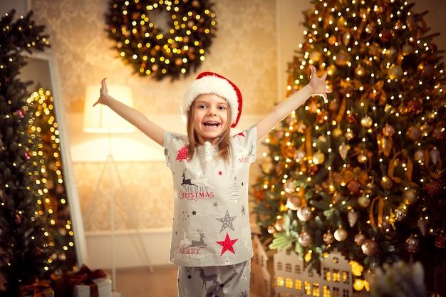 Chica alegre feliz en pijama de navidad, sombrero de ayudante de santa levantó sus manos.