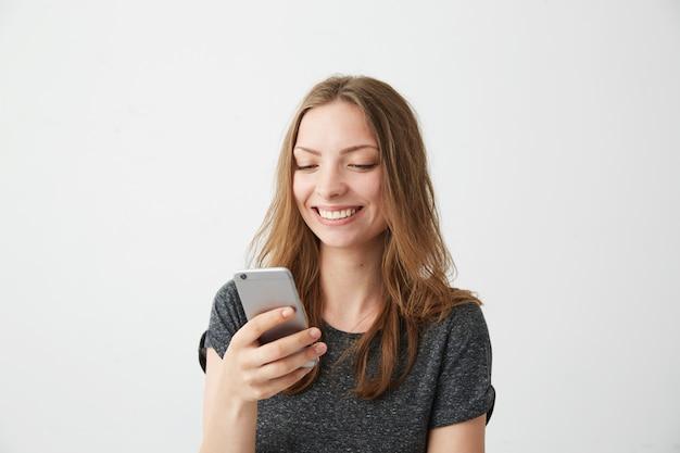 Chica alegre feliz sonriendo mirando la pantalla del teléfono escribiendo mensajes de texto.