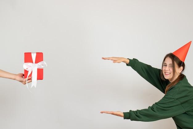 Chica alegre con gorro de fiesta tratando de determinar el tamaño del regalo en la mano humana sobre blanco