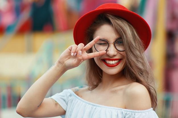 Chica alegre guiñando un ojo y sonriendo mientras muestra el signo de la victoria