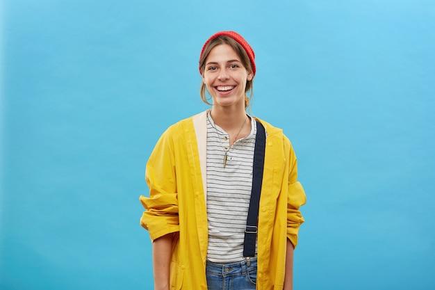 Chica alegre hipster en elegante impermeable amarillo y sombrero rojo