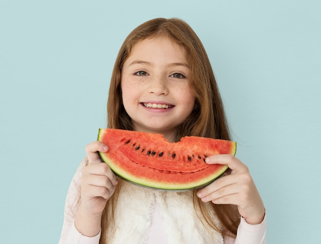 Chica alegre joven sosteniendo una rebanada de sandía