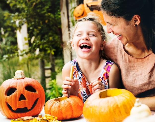 Chica alegre joven tallando calabazas con su mamá