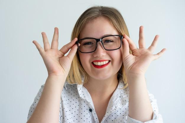 Chica alegre con labios rojos disfrutando de llevar gafas