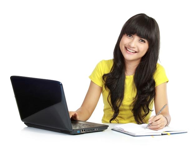 Chica alegre con laptop y escribir en libros, aislado