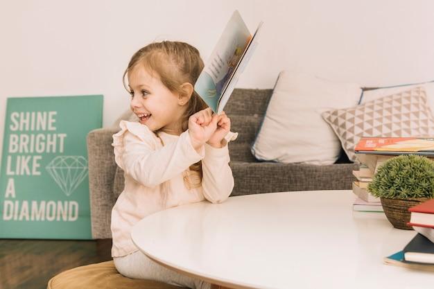 Chica alegre con el libro en la mesa