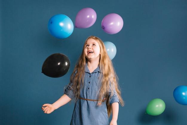 Chica alegre mirando globos Foto gratis