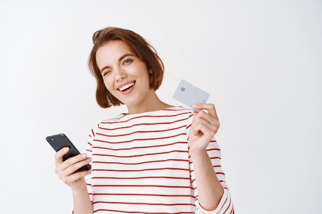Chica alegre pagando con smartphone en línea, mostrando tarjeta de crédito plástica para ir de compras y sonriendo, de pie contra la pared blanca