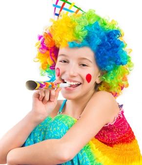 Chica alegre en peluca de payaso rizado y soplador de bocina de fiesta