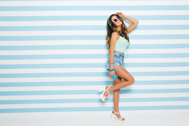 Chica alegre con piel bronceada con camiseta sin mangas y pantalones cortos bailando, escuchando música favorita. retrato de cuerpo entero de una mujer joven y bonita en auriculares con teléfono móvil divirtiéndose en casa.