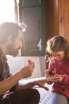 Chica alegre pintando las uñas del padre