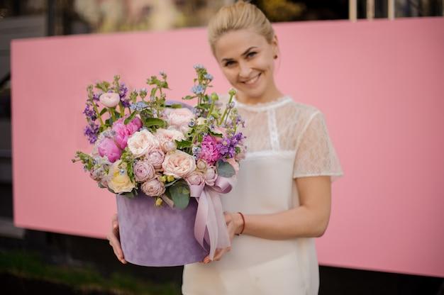 Chica alegre con ramo de flores con peonías en caja
