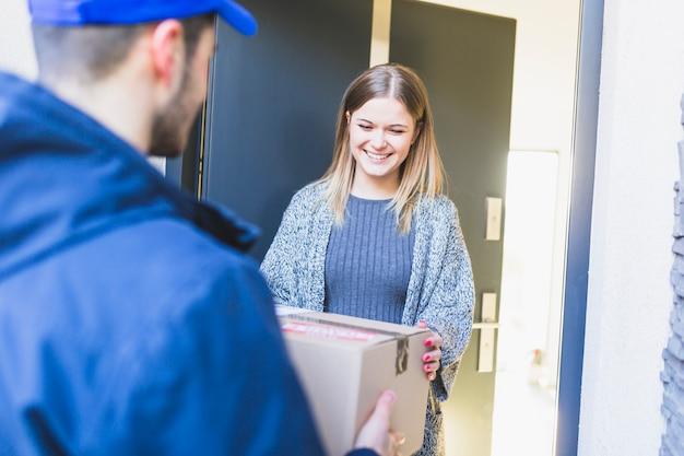 Chica alegre recibiendo caja entregada