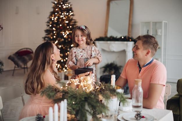 Chica alegre recibiendo regalos de navidad de los padres