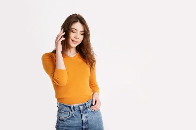 Una chica alegre se ríe mientras habla por un teléfono móvil. una morena está hablando por teléfono sobre un fondo claro con espacio para texto