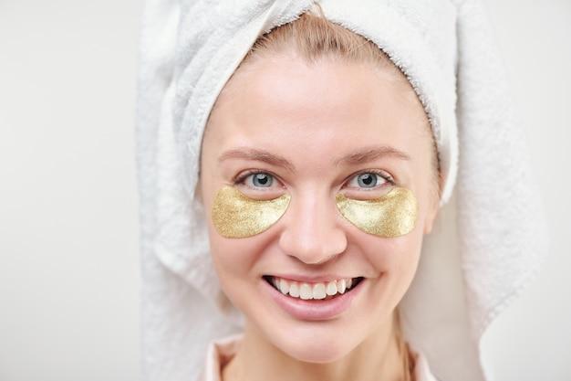 Chica alegre sana con una toalla en la cabeza y revitalizantes parches dorados debajo de los ojos de pie