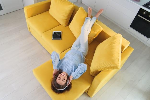 Chica alegre satisfecha tumbada en el cómodo sofá y escucha la música en sus auriculares blancos. vista superior.