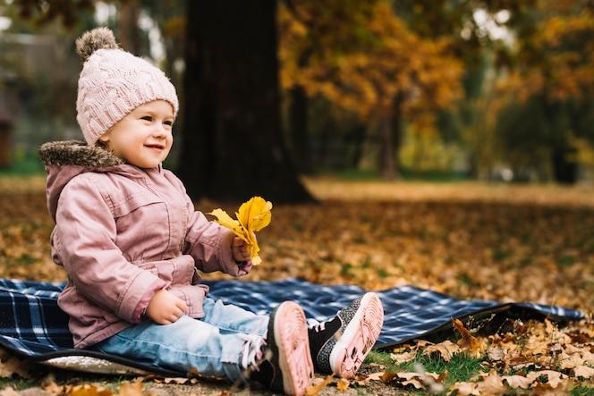 Chica alegre sentado sobre la base en el bosque de otoño