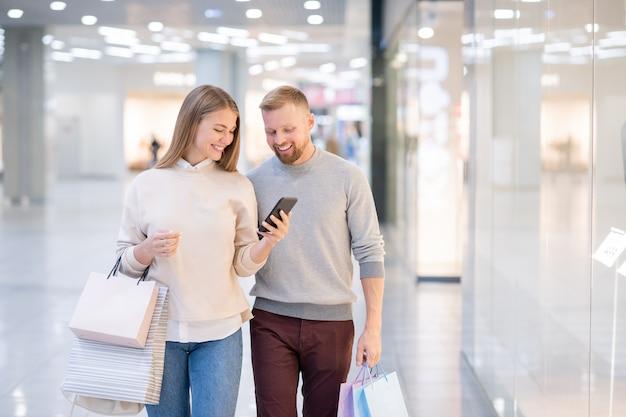 Chica alegre con smartphone y su novio mirando a través de productos en línea en la tienda de internet mientras se relaja en el centro comercial