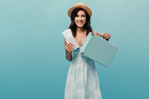 Chica alegre con sombrero de paja sosteniendo boletos y maleta sobre fondo azul.