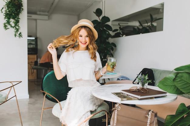 Chica alegre en sombrero vintage de moda jugando con cabello rubio y riendo relajándose en el café