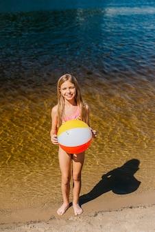 Chica alegre sosteniendo pelota de playa de pie contra el mar