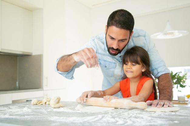 Chica alegre y su papá amasando y rodando masa en la mesa de la cocina con harina desordenada.