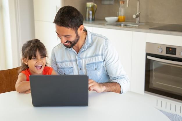 Chica alegre y su papá usando laptop para videollamadas, sentados a la mesa, viendo películas divertidas, mirando la pantalla.