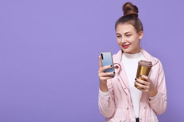Chica alegre tiene un descanso para tomar café, de pie con el dispositivo en las manos, lee la notificación en el teléfono móvil, actualiza la aplicación favorita, escribe mensajes y sonríe mientras mira la pantalla, usa chaqueta, copia espacio.