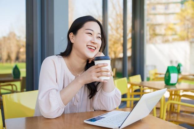 Chica alegre usando laptop para videollamada