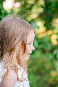 Chica alegre en vestido blanco jugando corre y se ríe al aire libre en el parque